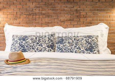 Female Hat And Pillow On The Bed Of A Hotel Room