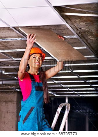 Woman in builder uniform installing suspended ceiling