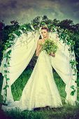 foto of wedding arch  - Beautiful elegant bride stands under the wedding arch - JPG