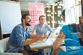 stock photo of conversation  - Young business partners sharing and discussing ideas at meeting in office - JPG