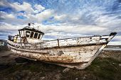 stock photo of junk-yard  - Old Boat on Abandoned Junk Yard with dramatic sky - JPG