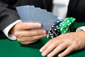 picture of gambler  - Gambler playing poker cards with chips on the table - JPG