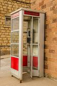 stock photo of phone-booth  - Red and white public telephone booth with a push button phone - JPG