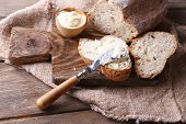 image of fresh slice bread  - Fresh bread and homemade butter on wooden background - JPG