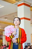 stock photo of polite girl  - Bright Thai college girl in academic gown is looking forward to the future in her graduation day - JPG