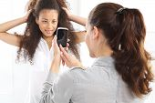 picture of two women taking cell phone  - Two women take pictures with your phone - JPG