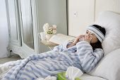 picture of common  - Young woman lying on bed with common cold - JPG