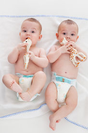 stock photo of twin baby  - two babies wear diapers and lie on a blanket - JPG