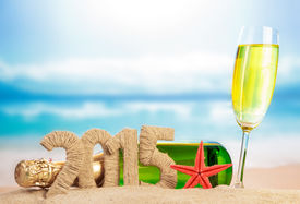 pic of champagne color  - Champagne and New year 2015 sign on sandy beach - JPG