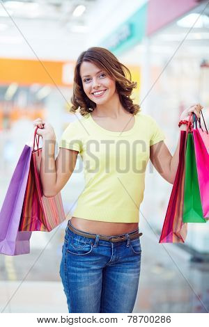Happy female shopaholic with shopping bags looking at camera