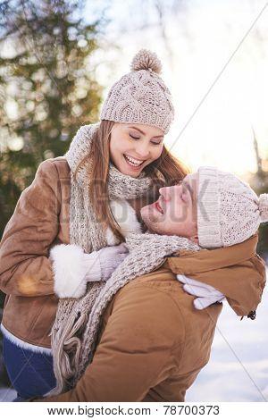Amorous and joyful couple having fun in winter outdoors