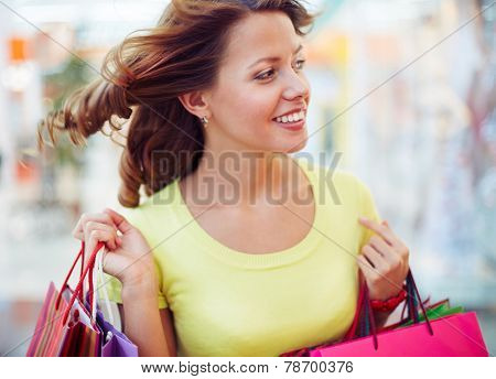 Interested shopaholic with paperbags looking for new gifts
