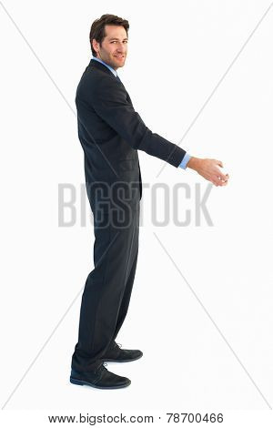 Smiling businessman reaching out to shake hands on white background