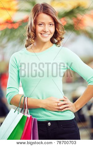 Pretty girl in casual-wear looking at camera after shopping