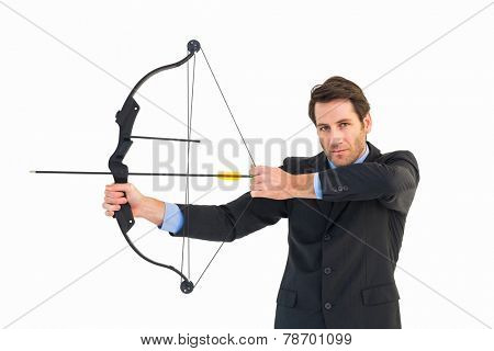 Serious businessman practicing archery looking at camera on white background