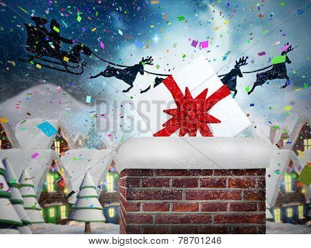 Santa flying his sleigh behind chimney against quaint town with bright moon