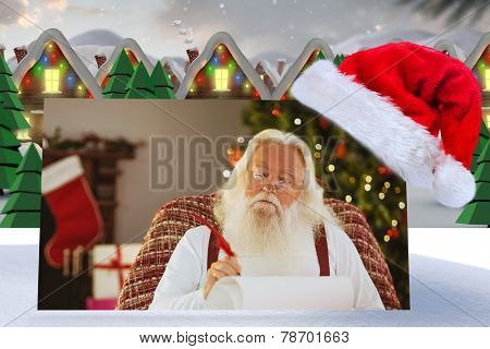 Relaxed santa writing list with a quill against quaint town with bright moon