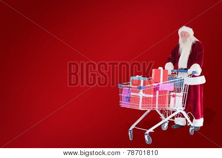 Santa pushes a shopping cart with presents against red background