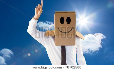Anonymous businessman with hand pointing up against bright blue sky with clouds
