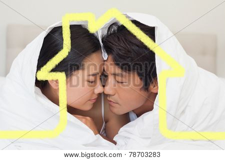 Happy couple lying on bed together under the duvet against house outline
