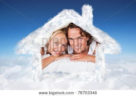 Couple under a duvet against blue sky over clouds