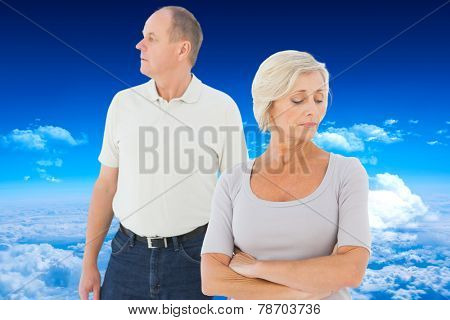 Older couple having an argument against mountain peak through clouds