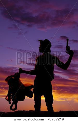 Silhouette Of Man Holding A Saddle In One Hand Gun In The Other