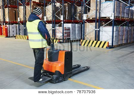 Electric forklift pallet stacker truck equipment at work in warehouse