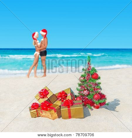 Couple In Santa Hats At Tropical  Beach With Christmas Tree And Golden Gifts