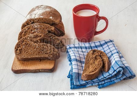 Sliced Rye Bread Tabatiere On A Cutting Board And  Red Cup With Milk On The Table