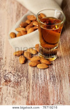 Dessert liqueur Amaretto with almond nuts, on wooden table