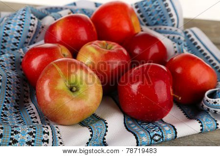 Heap of apples with dishcloth on wooden table background