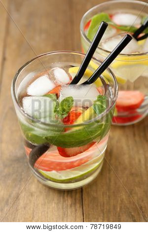 Summer cocktail with ice cubes on wooden table