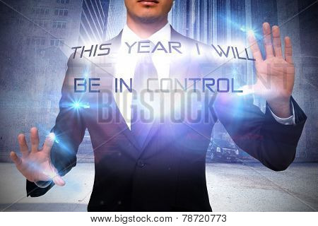 Unsmiling businessman touching against urban projection on wall