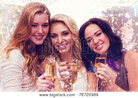 Pretty friends drinking champagne together against gold and red lights