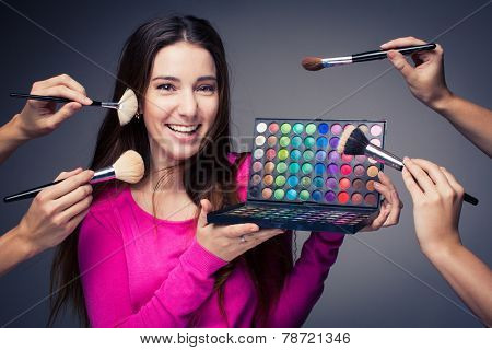 Cute make-up artist holding her vast palette of colors and hands with brushes around her (color toned image)