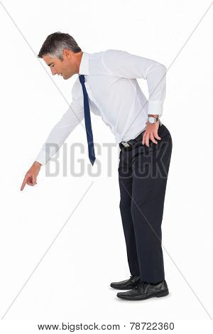 Businessman bending and pointing something down on white background