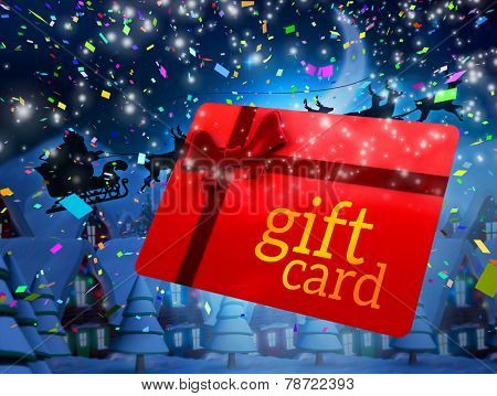 Santa flying his sleigh behind gift card against quaint town with bright moon