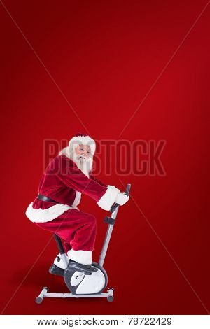 Santa uses a home trainer against red background