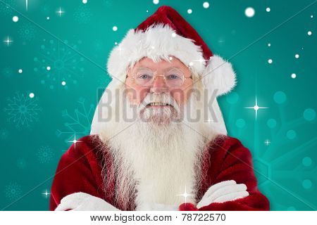 Santa smiles with folded arms against green snowflake background