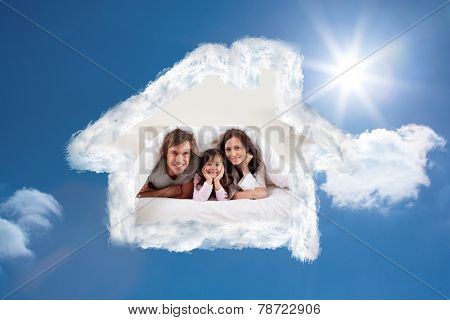 Smiling parents lying under a duvet with their daughter against bright blue sky with clouds
