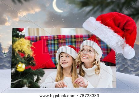 Festive mother and daughter decorating christmas tree against cute christmas village at north pole