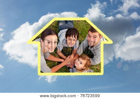 young Parents and kid lying on garden with hands together against cloudy sky
