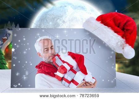 happy festive man with gifts against quaint town with bright moon