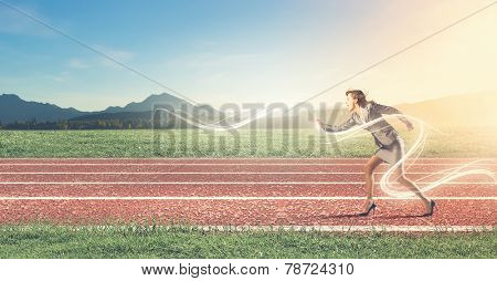 Young businesswoman in suit running on stadium track