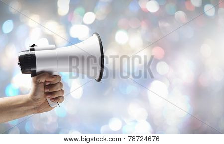 Close up of human hand holding megaphone