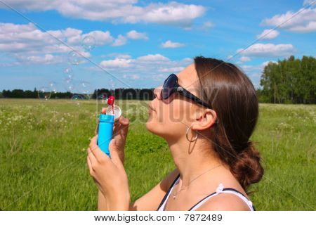 Woman blowing soap bubbles