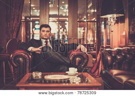 Confident handsome brunette sitting in luxury interior