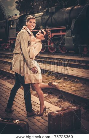 Vintage style couple with suitcases on train station platform