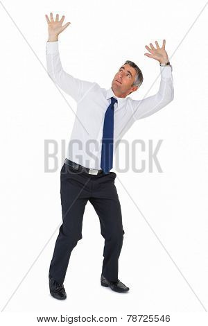 Businessman looking up with arms up on white background